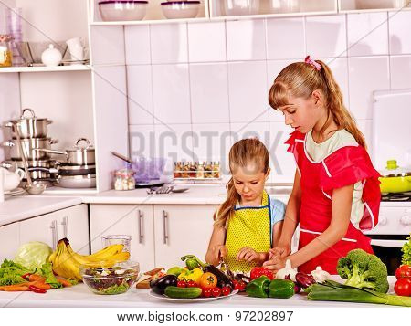 Children little girl cooking on their own at kitchen.