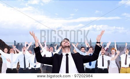 Businessman cheering with hands raised against large city on the horizon