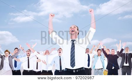 Handsome businessman cheering with arms up against cloudy sky
