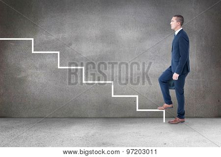 Businessman climbing against grey room