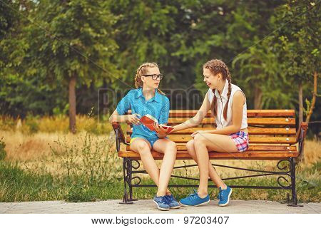 Best Friends Are Discussing Book Sitting On Bench.