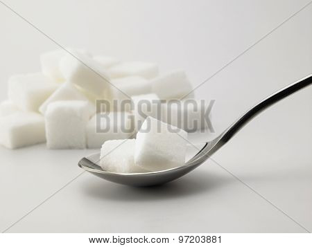 spoonful of sugar cubes on white