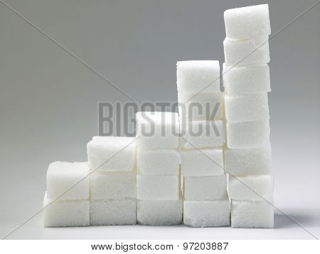 Ascending stacks of sugar cubes over gray background. This in a concept for high risk of diabetes or other diseases caused by excessive consumption of sugar
