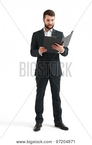 serious businessman in formal wear reading documents in black folder. isolated on white background