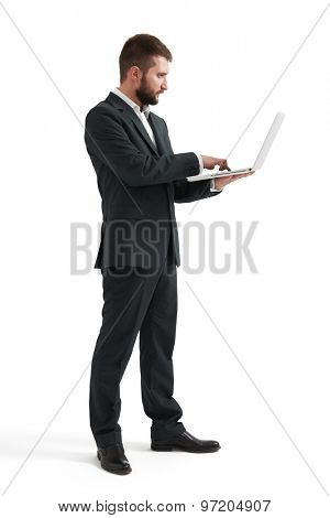 full length portrait of serious businessman working wit laptop. isolated on white background