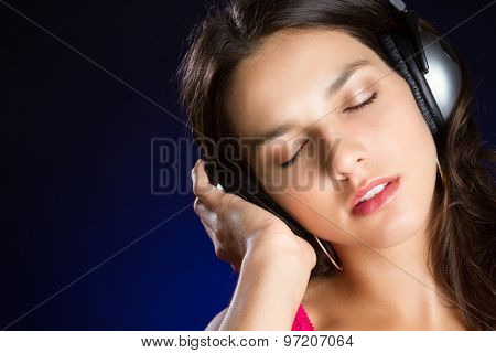 Beautiful teen girl listening to headphones music