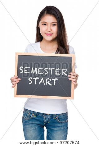Young woman hold with chalkboard and showing semester start on board