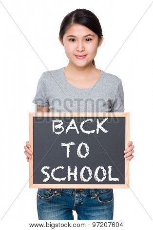 Woman hold with chalkboard and showing phrase of back to school