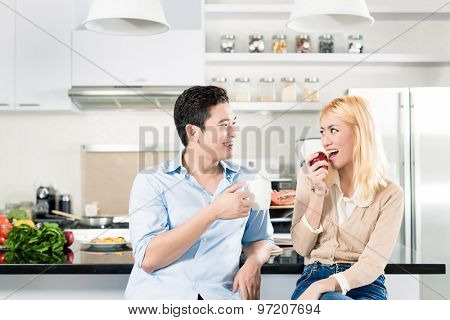 Asian couple having breakfast together in modern apartment