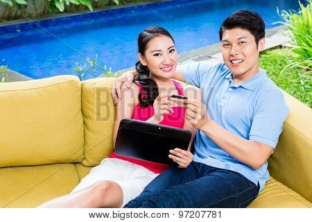 Asian couple shopping online in internet with laptop and credit card