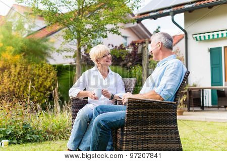Couple of man and woman sitting in front of their home or house in wicker chairs