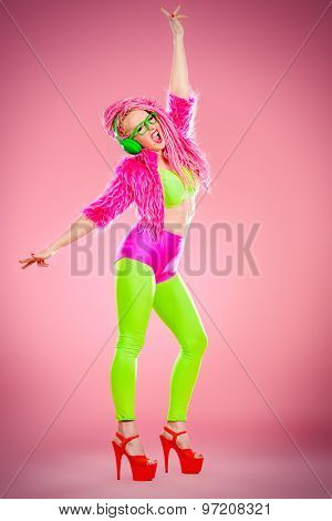 Full length portrait of a dancing glamorous show girl in bright clothes, headphones and with bright pink dreadlocks. Disco, party. Show business. Bright fashion.