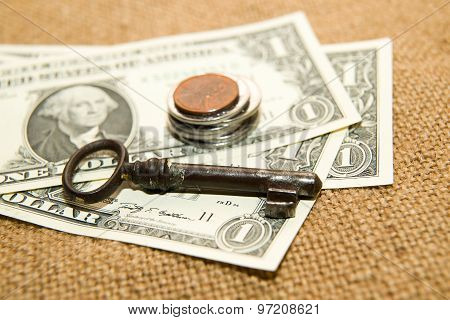 Us Dollars Banknotes, Coins And Key On An Old Cloth