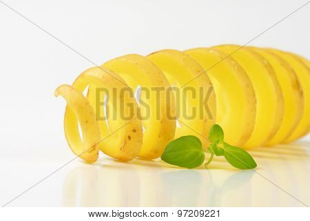 close up of potato peel spiral on white background