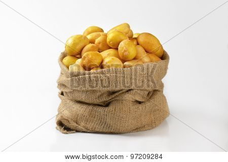 burlap sack of fresh baby potatoes on white background