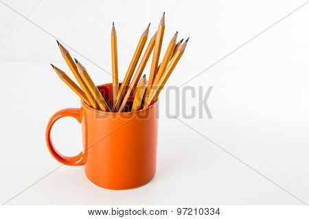Orange mug with pencils