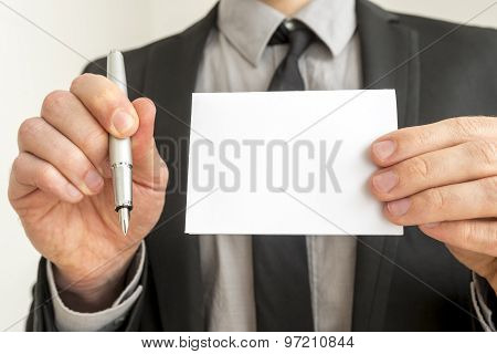 Businessman Holding Pen And Empty White Paper
