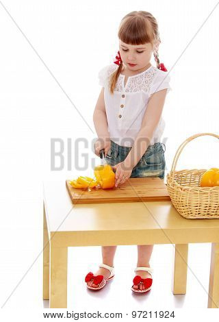 little girl with a knife cuts vegetables