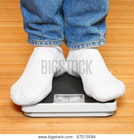 Overweight woman in socks standing on a weighing machine.