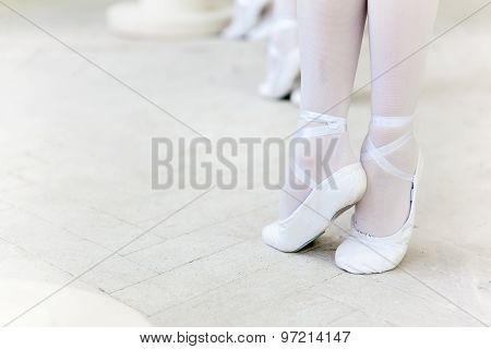 Three little ballerinas dancing. legs in ballet flats close-up