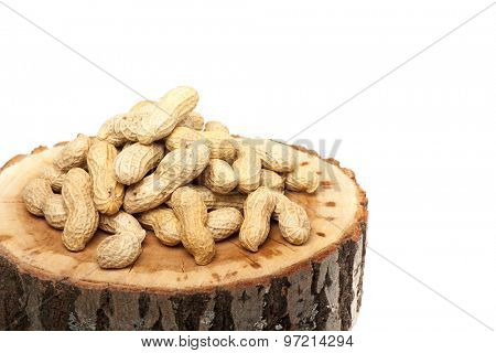 Pile of unshelled peanuts on wood slice, isolated on white background