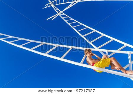 young thoughtful kid - boy - climbing white ladders going nowhere up on natural sky background, outdoor