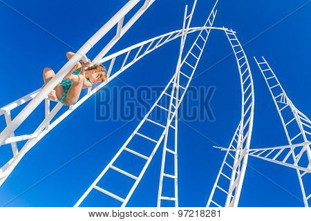 young happy kid - girl - climbing white ladders going nowhere up on natural sky background, outdoor