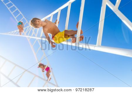young happy kids - boy and girl - climbing white ladders going nowhere up on natural sky background, outdoor