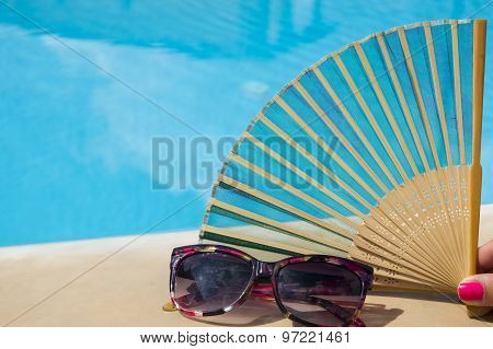 Hand-fan In Girls Hand Next To Sunglasses With Clear Blue Water In Background. Summer Heat Concept