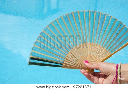 Hand Fan In Girls Hand With Clear Blue Water In Background. Save From The Heat