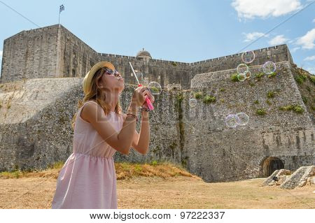 Girl Blowing Soap Bubbles In The Greak Fortress On Corfu Wearing Straw Hat And Pink Dress