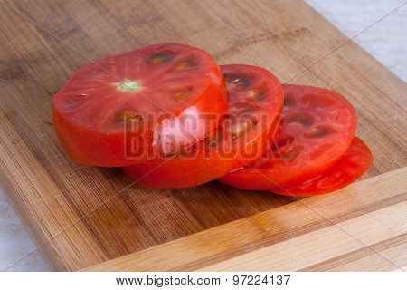 Freshly Slised Tomato On A Wooden Cutting Board