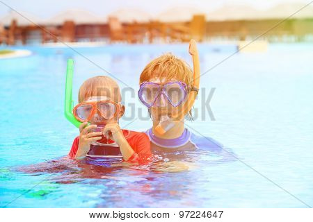 father and little son snorkeling on tropical beach