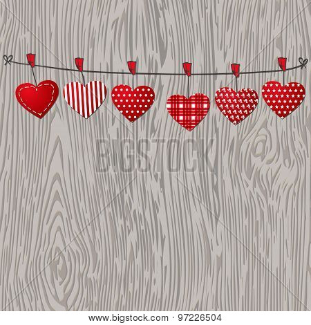 Love Valentines hearts hanging on texture wood background.