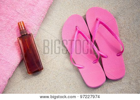 Pink Flip Flops And Suntan Lotion Bottle On Sandy Beach