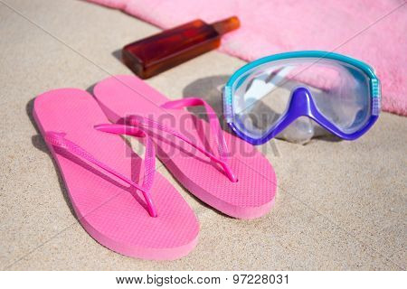 Summer Concept - Flip Flops, Towel, Diving Mask And Suntan Lotion Bottle On Sandy Beach