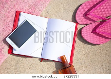 Notepad And Smart Phone On Sandy Beach Background