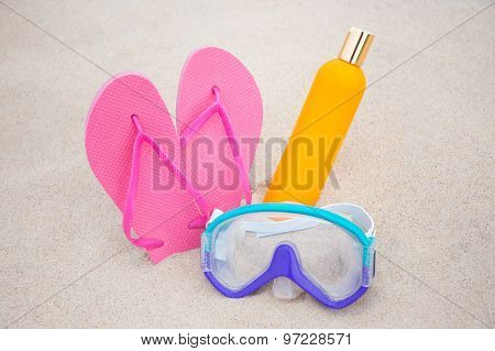 Summer Concept - Diving Mask, Slippers And Suntan Lotion Bottle On Sandy Beach