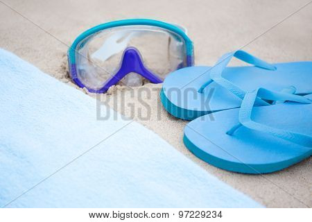 Beach Concept - Blue Flip Flops, Towel And Diving Mask On The Sand