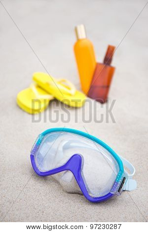 Diving Concept - Mask, Slippers And Suntan Lotion Bottles In Sand