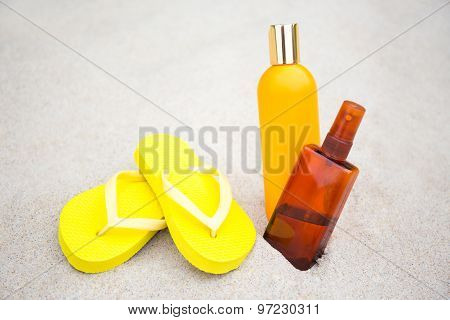 Skin Care Concept - Flip Flops And Suntan Lotion Bottles In Sand