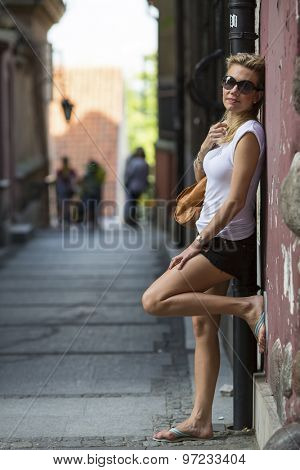 Beautiful blonde woman stands in the street of old district. Travelling.