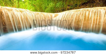 Fresh water river flows and falls from waterfall cascade. Smooth and silky stream nature background