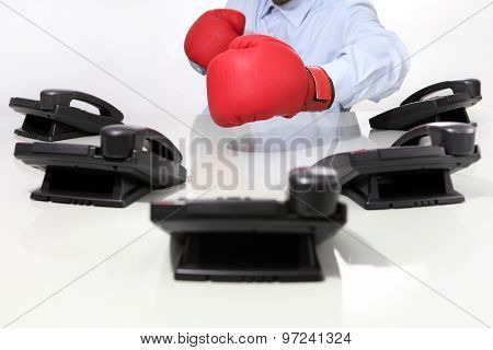 Operator In Office With Boxing Gloves And Phones On Desk.