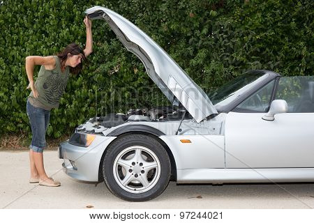 Woman Opens Car Hood And Tries To Repair The Broken Car On The Road
