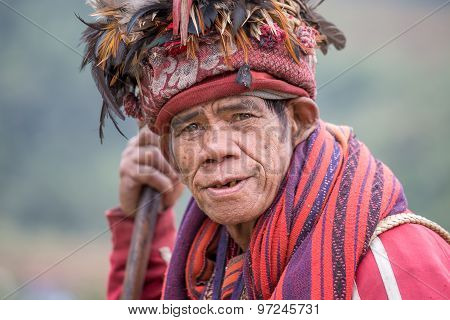 old ifugao man in national dress next to rice terraces.