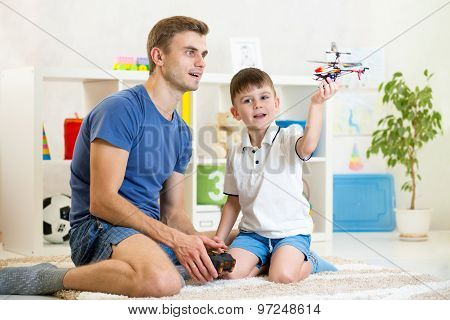 Father and his son play with RC helicopter toy