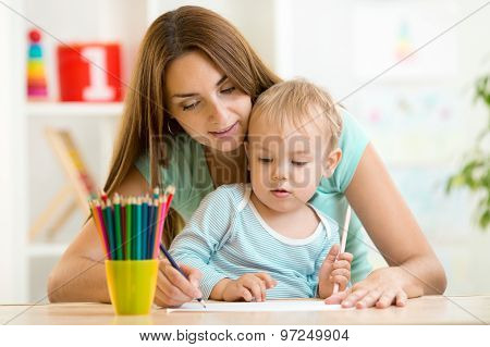 Mother and toddler child draw and paint together