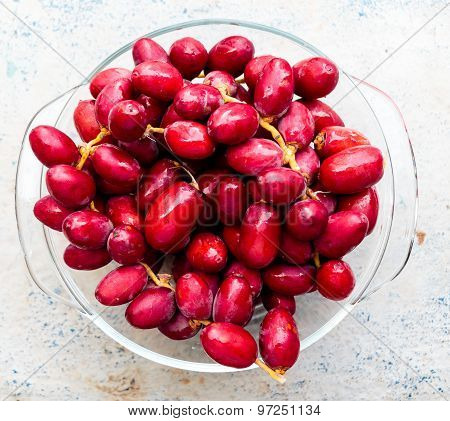 Fresh raw reddish pink date palm fruits taken out from refrigerator and kept on a bowl