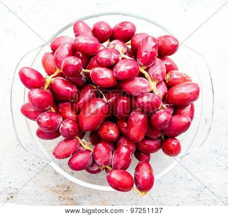 Freshly plucked raw reddish pink date palm fruits with dew drop on it and kept on a bowl